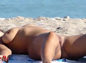 Naturist woman sunbathing nude on the..